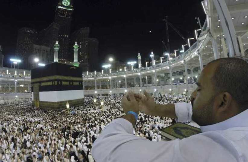 A Muslim pilgrim prays around the holy Kaaba at the Grand Mosque in Mecca (photo credit: REUTERS)