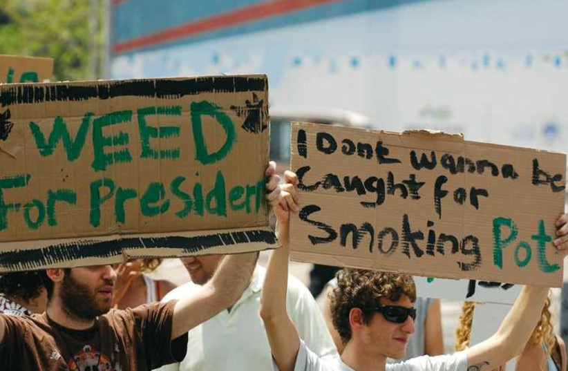 Demonstrators hold signs at a 2010 rally in Tel Aviv for the legalization of marijuana. (photo credit: REUTERS)