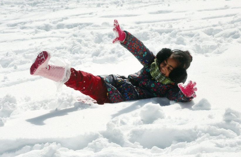 A child plays in the snow in Jerusalem in February. (photo credit: MARC ISRAEL SELLEM/THE JERUSALEM POST)