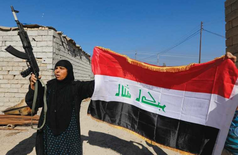 A WOMAN raises a weapon and the Iraqi flag in celebration after Iraqi government troops and militias drove Islamic State insurgents out of the town of al-Alam on Tuesday, clearing a final hurdle for an assault on the city of Tikrit. The Arabic characterson the flag read, 'God is the greatest.' (photo credit: REUTERS)