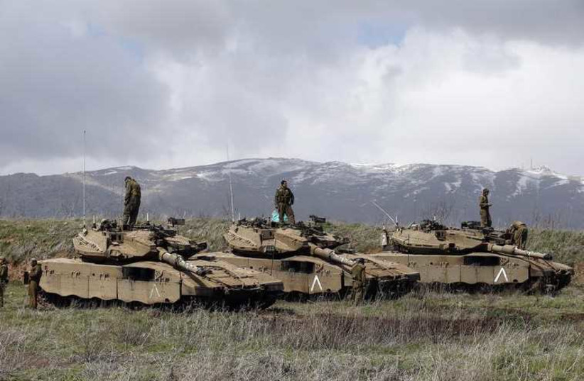 Israeli soldiers stand atop tanks in the Golan Heights near Israel's border with Syria (photo credit: REUTERS)