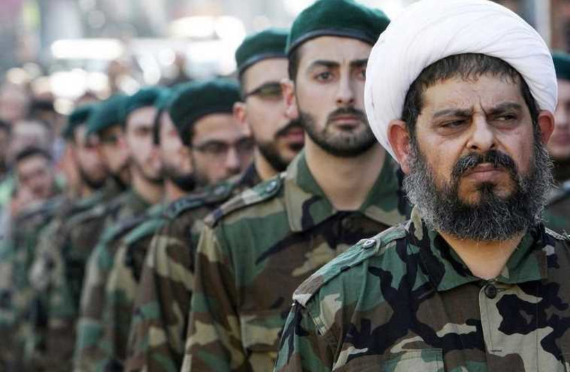 A Shi'ite cleric wearing military uniform with Hezbollah members. (photo credit: REUTERS)