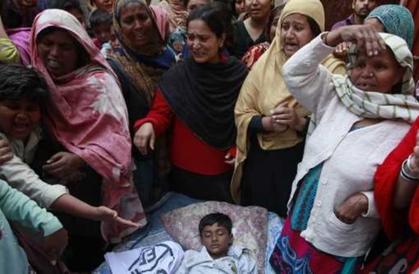 People mourn as they surround the body of their relative who was killed in a suicide attack on a church in Lahore  (photo credit: REUTERS)