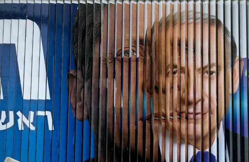Prime Minister Benjamin Netanyahu and Isaac Herzog, Co-leader of the centre-left Zionist Union, are pictured together as campaign billboards rotate in Tel Aviv (photo credit: REUTERS)