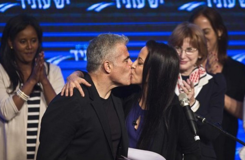 Yesh Atid leader Yair Lapid and his wife Lihi kiss at a women's committee convention in Tel Aviv (photo credit: REUTERS)