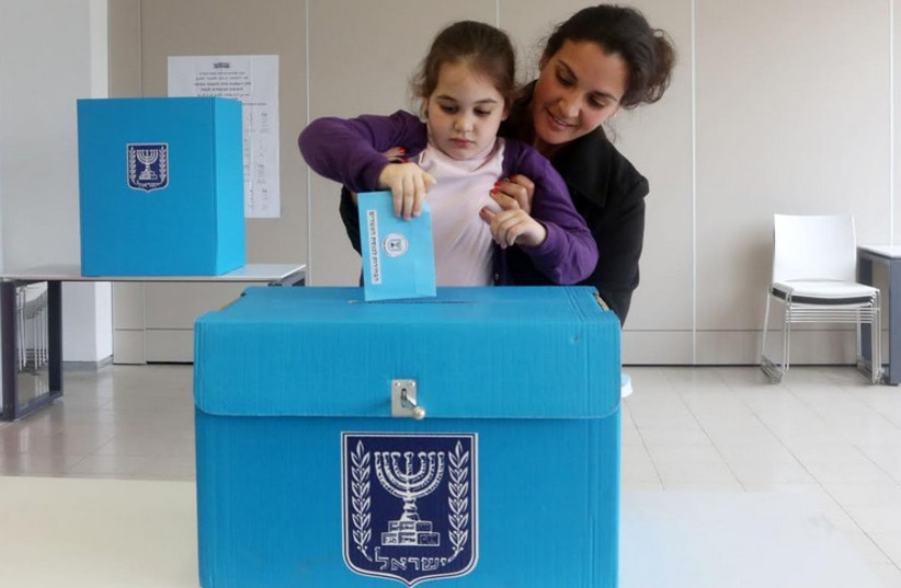 A child casts her mother's vote (photo by Marc Israel Sellem) (photo credit: MARC ISRAEL SELLEM)
