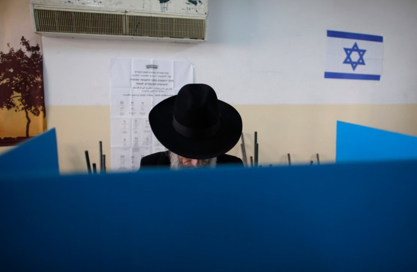 A ultra-Orthodox Jewish man stands behind a voting booth at a polling station  (photo credit: REUTERS)