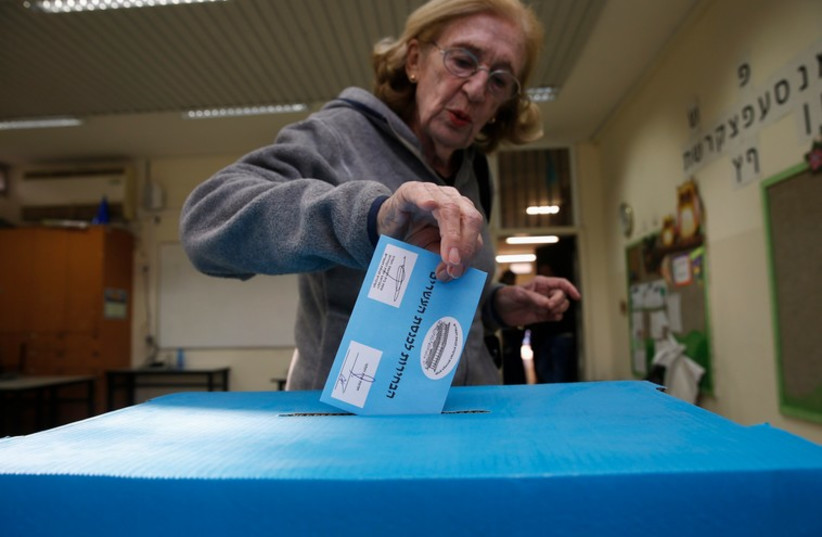 An Israeli casts her ballot for the parliamentary election at a polling station  (photo credit: REUTERS)