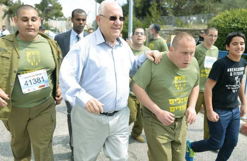 PRESIDENT REUVEN RIVLIN runs a stretch of the Jerusalem Marathon with Great in Uniform special-needs persons who have volunteered for the IDF (photo credit: MEIR ALFASSI)