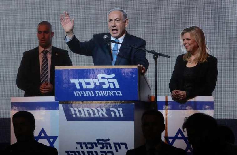 Prime Minister Benjamin Netanyahu gestures during his victory speech at Likud headquarters as his wife, Sara, looks on (photo credit: MARC ISRAEL SELLEM)