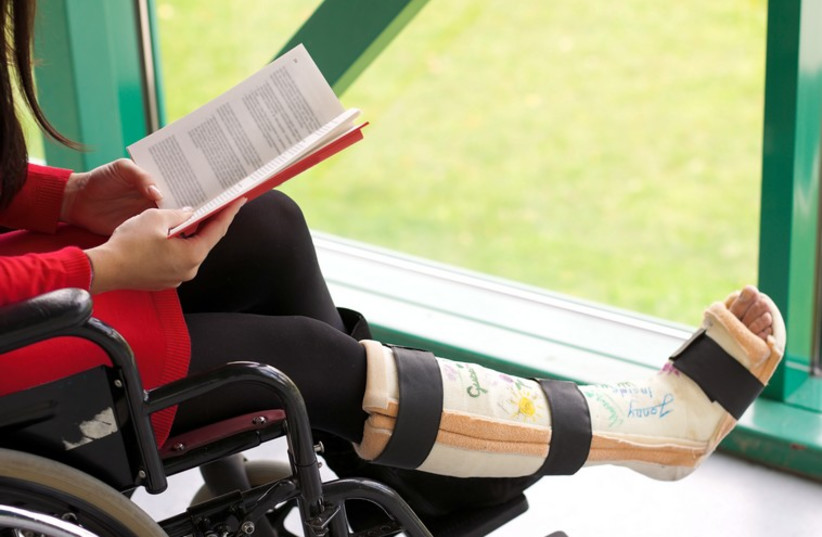Young woman in a wheelchair with leg in plaster (illustrative). (photo credit: INGIMAGE)
