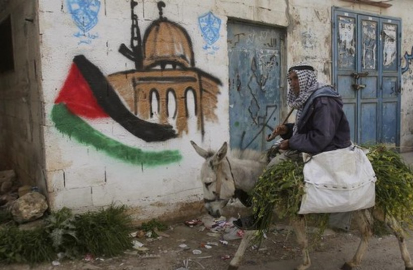 A Palestinian villager rides his donkey past a mural in the West Bank village of Awarta near Nablus (photo credit: REUTERS)