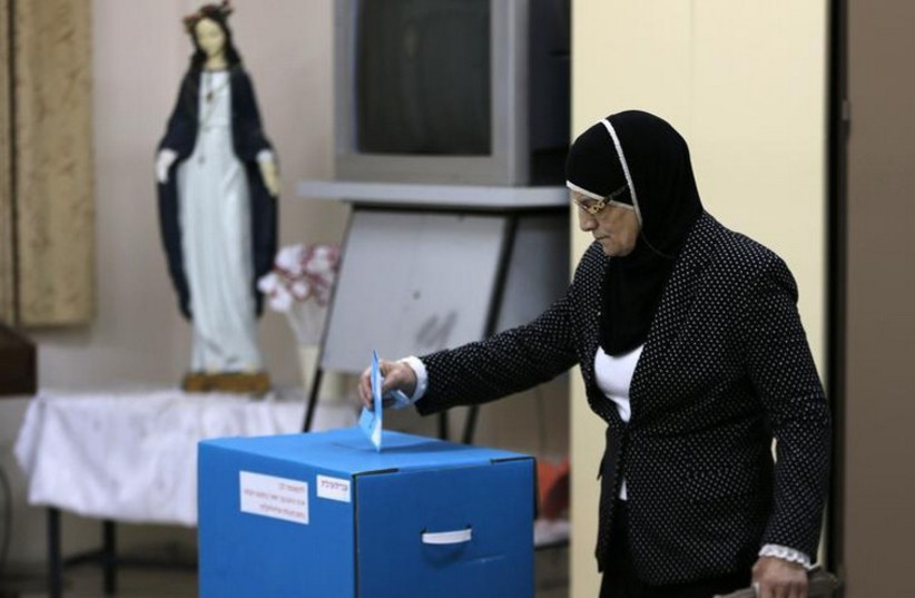 An Israeli Arab casts her ballot at a polling station inside a church in the northern town of Reineh (photo credit: REUTERS)