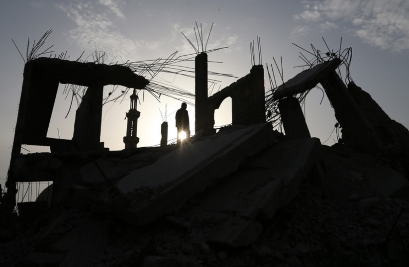 A Palestinian man walks atop the remains of a house that witnesses said was destroyed by Israeli shelling during a 50-day war last summer, in the southern Gaza Strip, March 10 (photo credit: REUTERS)