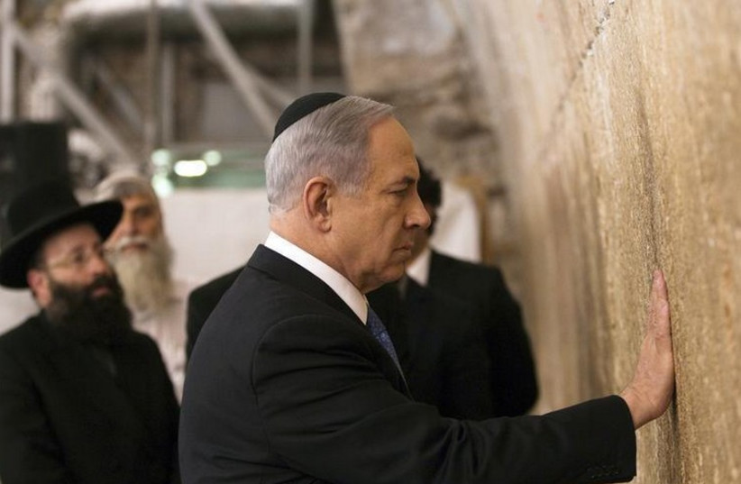 Prime Minister Benjamin Netanyahu touches the stones of the Western Wall (photo credit: REUTERS)
