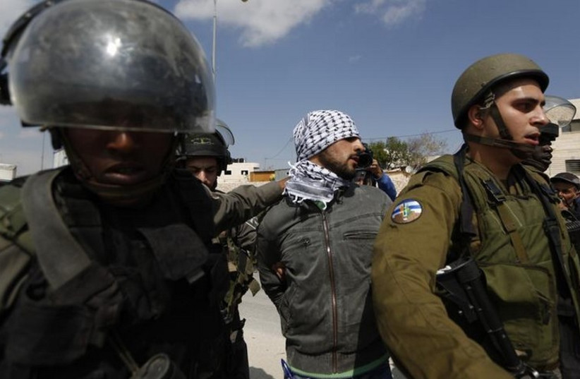 Israeli security forces detain a Palestinian near the West Bank town of Abu Dis (photo credit: REUTERS)