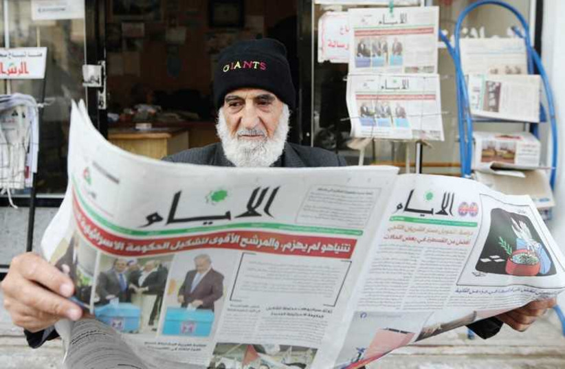 A Gaza man reads a newspaper, featuring the Israeli election on its front page, in Khan Younis, March 18. (photo credit: IBRAHEEM ABU MUSTAFA / REUTERS)