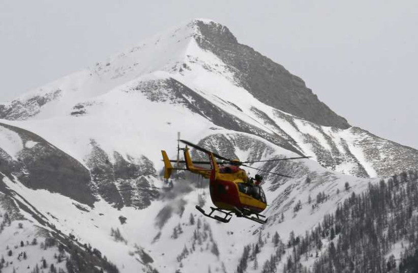 A rescue helicopter from the French Securite Civile flies over the French Alps during a rescue operation near the crash site of an Airbus A320. (photo credit: REUTERS)
