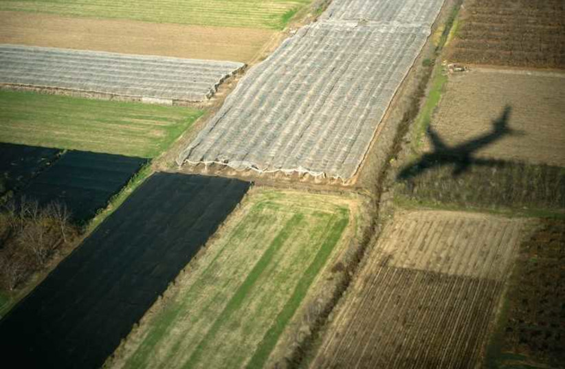 A plane flies over a field (ILLUSTRATIVE) (photo credit: REUTERS)