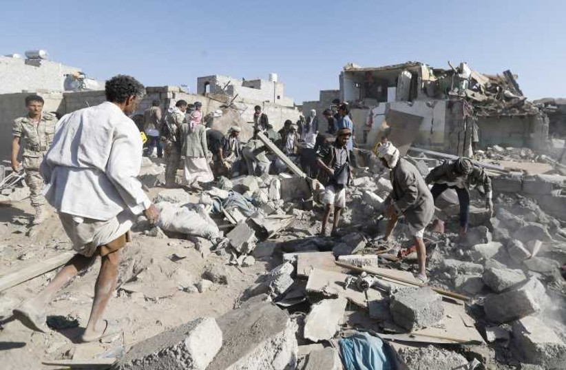 People search for survivors under the rubble of houses destroyed by an air strike near Sanaa Airport. (photo credit: REUTERS)