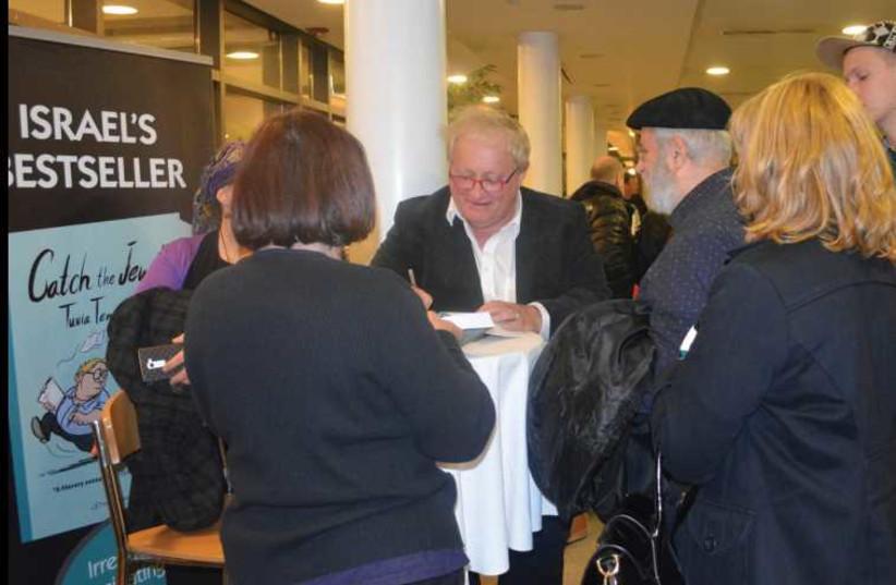 Tuvia Tenenbom signs copies of his books. (photo credit: GEFEN PUBLISHING)