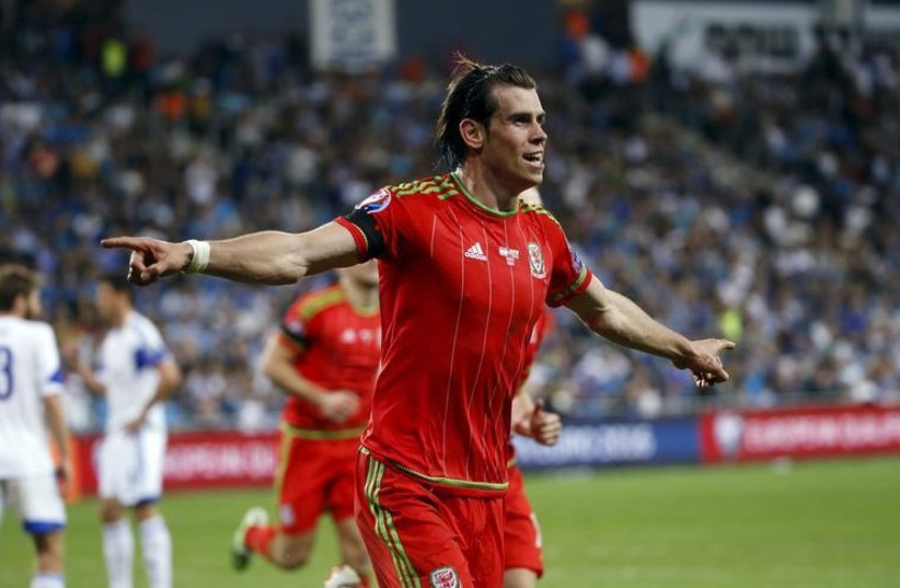 Wales' Gareth Bale celebrates scoring a goal against Israel during their Euro 2016 Group B qualifying soccer match at the Sammy Ofer Stadium in Haifa (photo credit: REUTERS)
