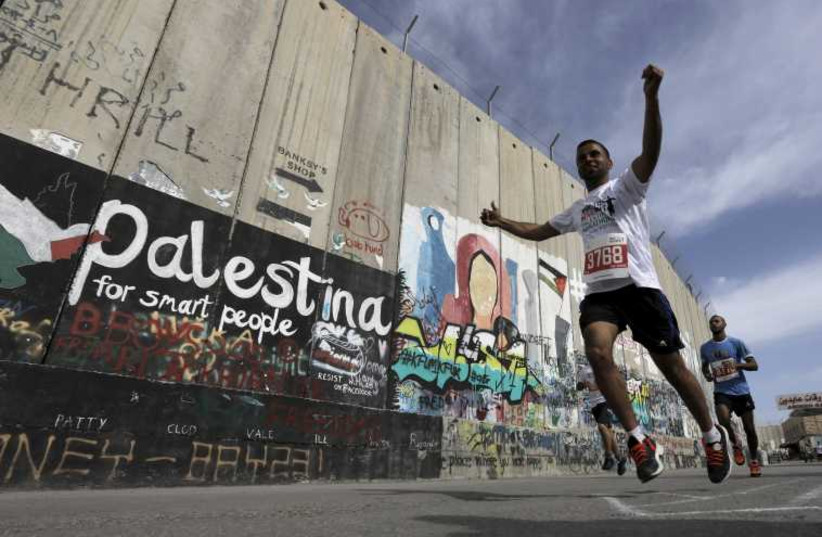 Participants run past Israeli barrier during Palestine Marathon in the West Bank town of Bethlehem. (photo credit: REUTERS)