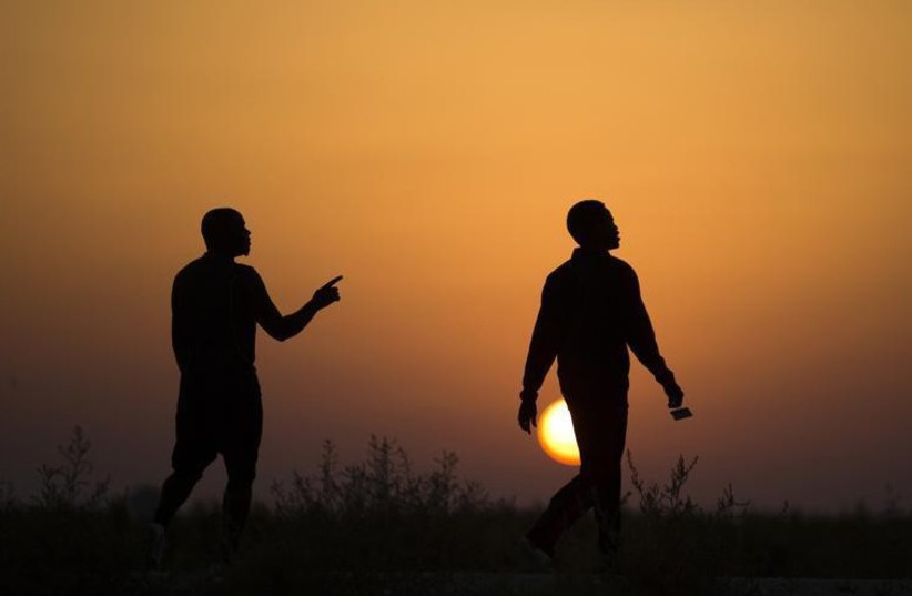 African migrants walk outside Holot open detention center in Israel's southern Negev desert (photo credit: REUTERS)