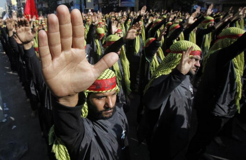 Lebanese Hezbollah supporters gesture as they march during a religious procession to mark Ashura in Beirut's suburbs (photo credit: REUTERS)