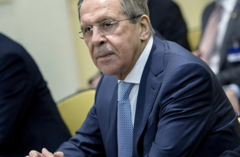 Russian Foreign Minister Sergei Lavrov (C) waits with others for a P5+1 meeting at the Beau Rivage Palace Hotel in Lausanne (photo credit: REUTERS)