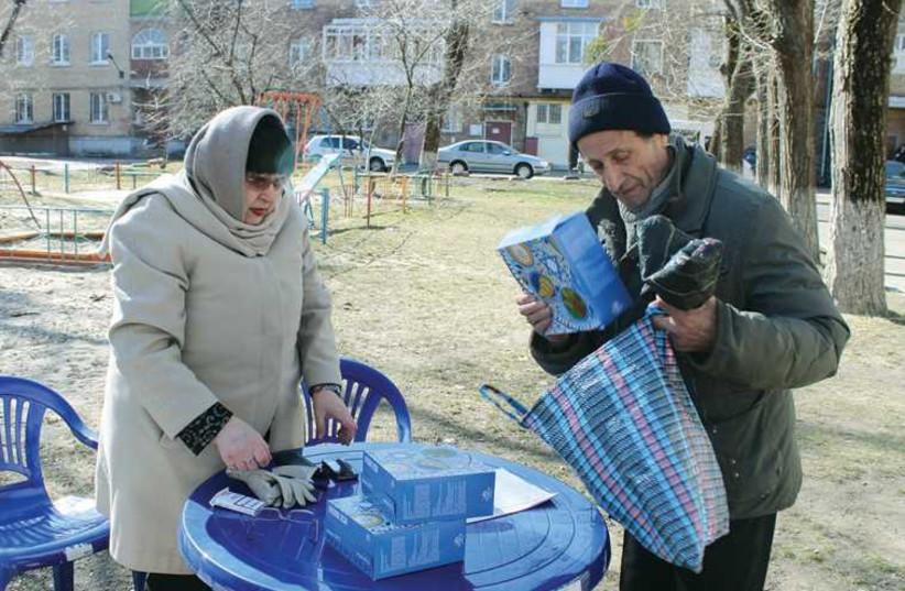 A JOINT Distribution Committee worker distributes matzot in Kiev last week. (photo credit: SAM SOKOL)