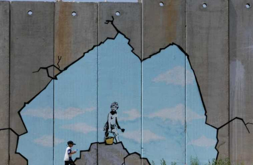 A Palestinian boy walks past a drawing by British graffiti artist Banksy (photo credit: REUTERS)