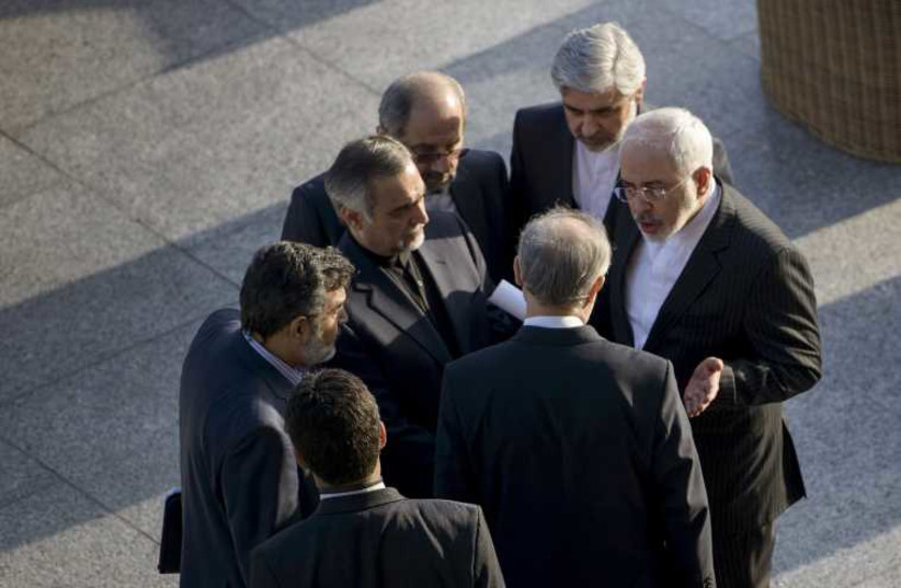 Iranian Foreign Minister Javad Zarif (R) and Head of Iranian Atomic Energy Organization Ali Akbar Salehi talk while other members of their delegation listen after a meeting with US Secretary of State John Kerry and American officials at the Beau Rivage Palace Hotel in Lausanne  (photo credit: REUTERS)