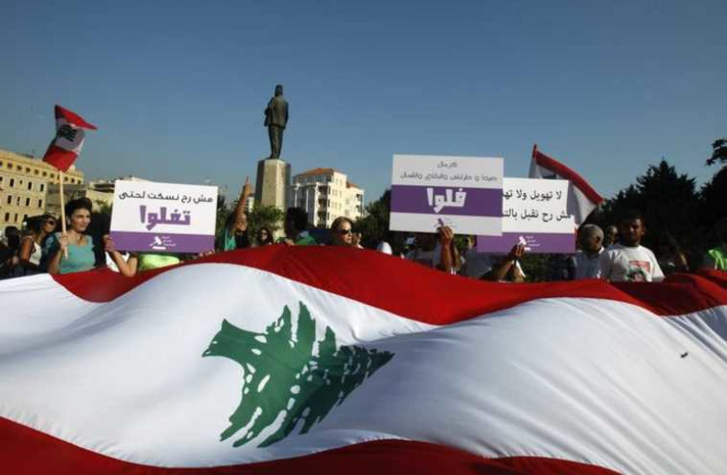 Activists and members of civil society organizations hold placards as they carry a giant Lebanese flag during a protest against the extension of the parliament terms (photo credit: REUTERS)