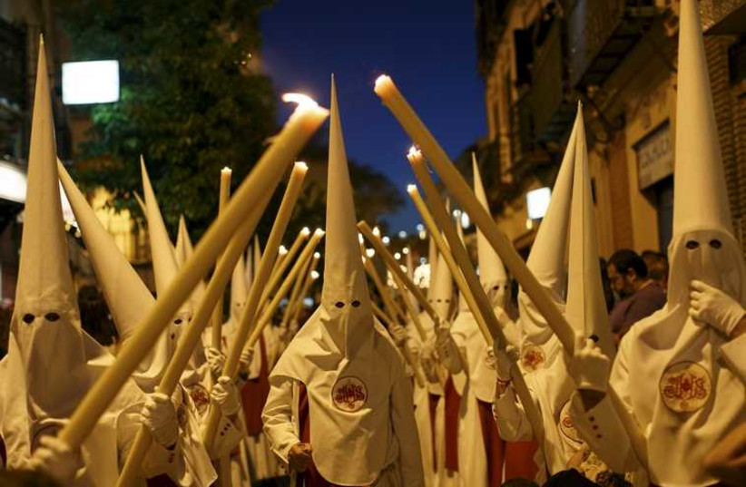Penitents of the Siete Palabras (Seven Words) brotherhood make their penance during a Holy Week procession in the Andalusian capital of Seville, southern Spain (photo credit: REUTERS)