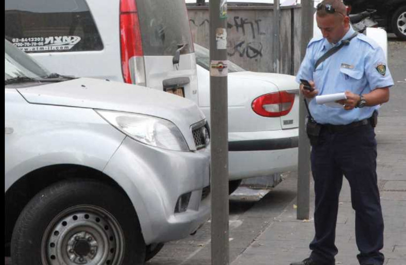 An inspector issues a parking ticket on Hillel Street. (photo credit: MARC ISRAEL SELLEM/THE JERUSALEM POST)