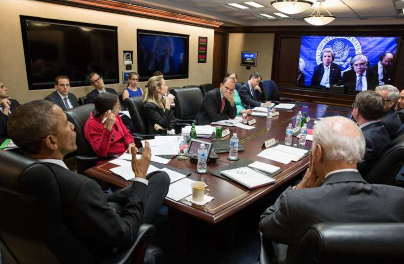 President Barack Obama, Vice President Joe Biden, and White House aides receive an update from Secretary of State John Kerry and Secretary of Energy Ernest Moniz via teleconference in Lausanne (photo credit: WHITE HOUSE)