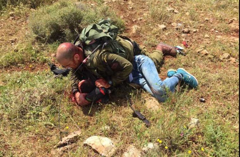 An IDF soldier subdues a Palestinian assailant after he was stabbed near a West Bank checkpoint (photo credit: IDF SPOKESMAN'S UNIT)