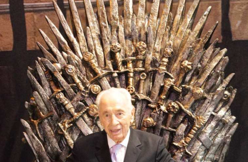 Former president Shimon Peres sits on a replica throne from the hit show 'Game of Thrones' (photo credit: YES)