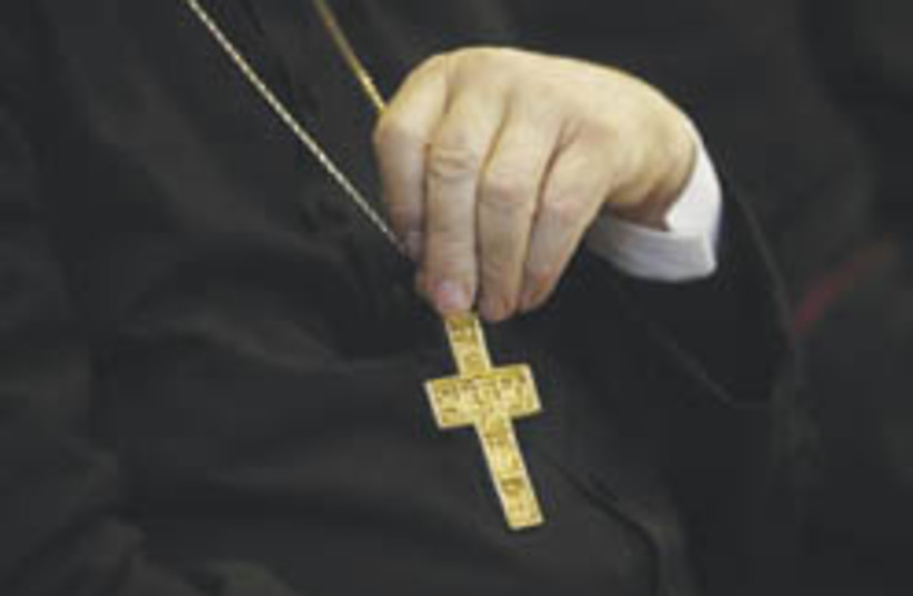 hand with crucifix  (photo credit: AP)