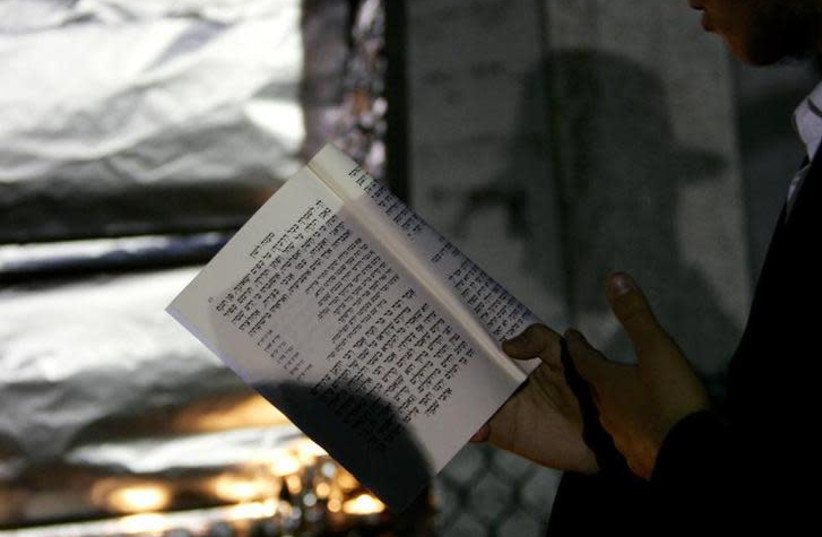 A man reads a prayer book outside (photo credit: SHANNON STAPLETON / REUTERS)