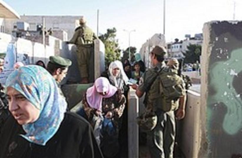 Border policeman checks Palestinians 248 (photo credit: )