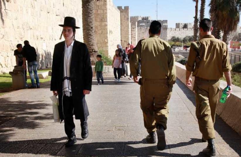 Haredi man and IDF soldiers in Jerusalem. (credit: MARC ISRAEL SELLEM)