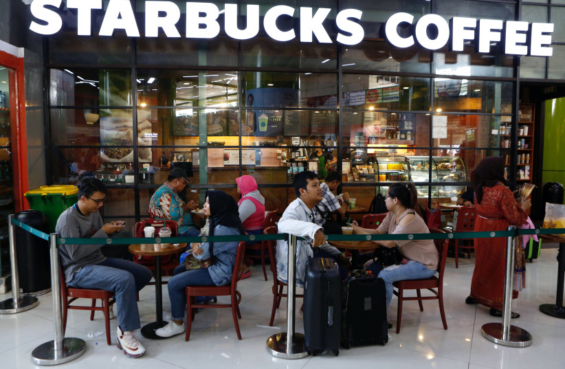 Customers sit outside of a Starbucks cafe in Jakarta, Indonesia July 1, 2017. (photo credit: REUTERS)