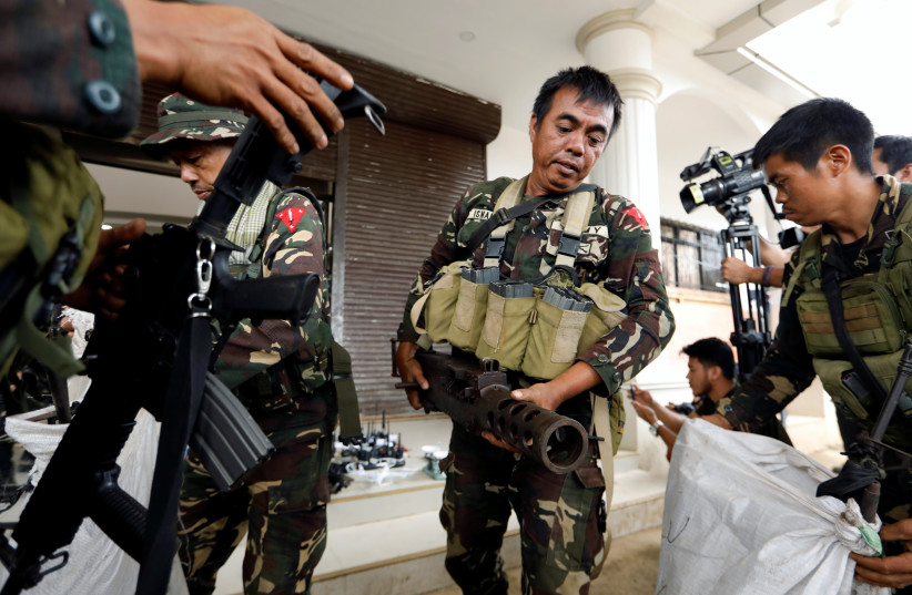 Philippines army soldiers store seized combat weapons in bags as government troops continue their assault against insurgents in Marawi city, Philippines July 4, 2017.  (photo credit: REUTERS/JORGE SILVA)