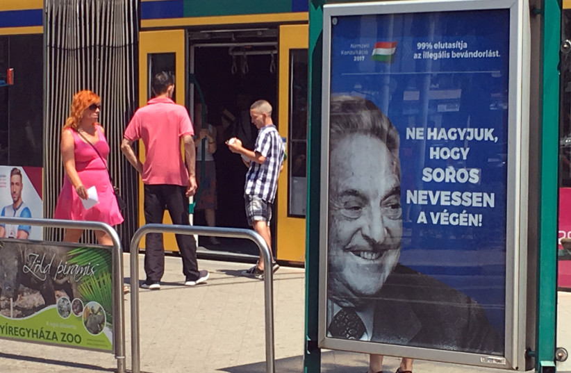 """Hungarian government poster portraying financier George Soros and saying """"Don't let George Soros have the last laugh"""" is seen at a tram stop in Budapest, Hungary (photo credit: REUTERS/KRISZTINA THAN)"""