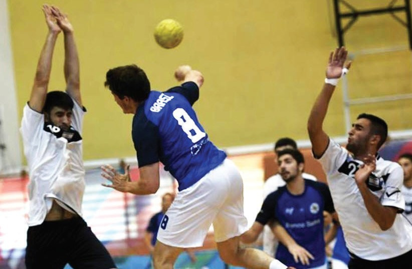 Israel's handball team (in white) defeated Brazil 33-25 in the Maccabiah final on Friday.  (photo credit: AMIT SCHUSSEL)
