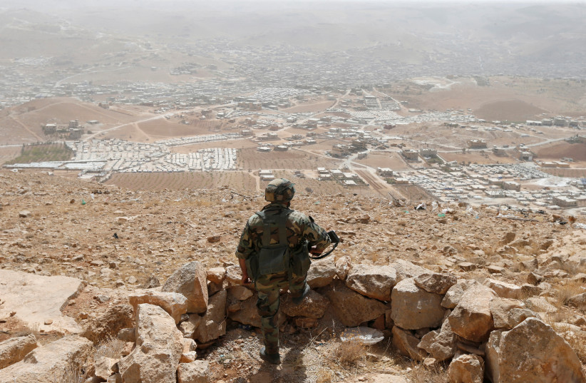 A Lebanese soldier carries his weapon as he stands at an army post in the hills above the Lebanese town of Arsal, near the border with Syria, Lebanon September 21, 2016. Picture taken September 21, 2016.  (photo credit: MOHAMED AZAKIR / REUTERS)