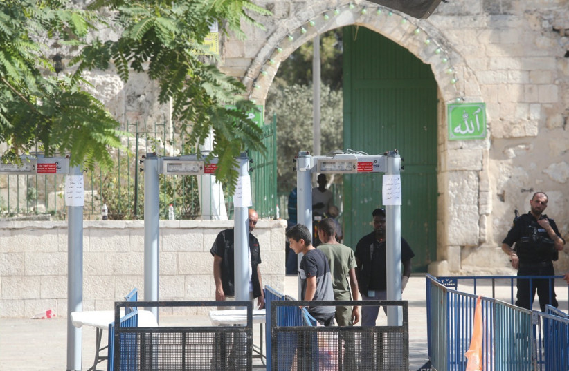BOYS PASS THROUGH metal detectors just inside the Old City's Lions' Gate in the capital yesterday, on their way to enter the Temple Mount. (photo credit: MARC ISRAEL SELLEM/THE JERUSALEM POST)