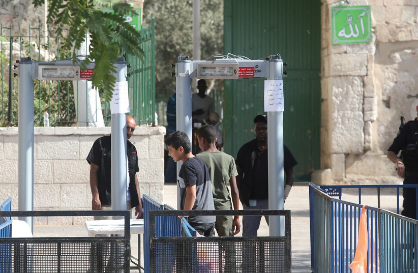 POLICE OFFICERS man a metal detector placed this week at an entrance to the Temple Mount (photo credit: MARC ISRAEL SELLEM/THE JERUSALEM POST)